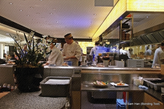 Chefs at work behind the sushi train counter.