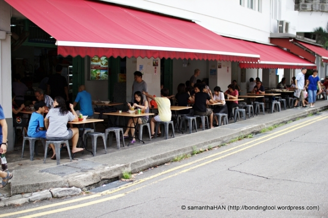 The lady with an orange plastic bag on the table - that was where I was sitting earlier enjoying my plate of wanton mee.