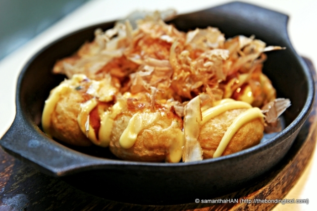 Takoyaki (たこ焼き or 蛸焼) is a ball-shaped Japanese snack made of a wheat flour-based batter and cooked in a special takoyaki pan. It is typically filled with minced or diced octopus (tako), tempura scraps (tenkasu), pickled ginger, and green onion. Takoyaki are brushed with takoyaki sauce, similar to Worcestershire sauce, and mayonnaise. The takoyaki is then sprinkled with green laver (aonori) and shavings of dried bonito (katsuobushi).  Info credit - Wikipedia