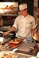 This chef was in charged of hotplate grilling lamb chops and fish.