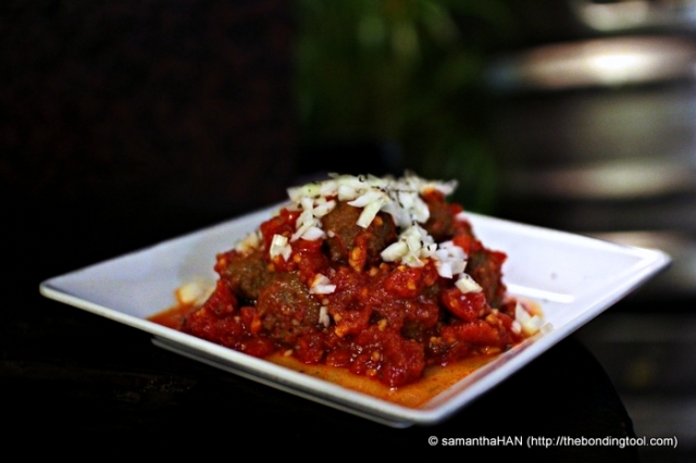 Italian Meatballs in Tomato Sauce topped with raw onions.