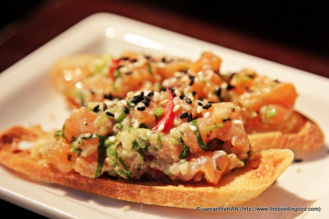 Salmon Ceviche Lemon and sesame marinated salmon dices on melba-like toast.