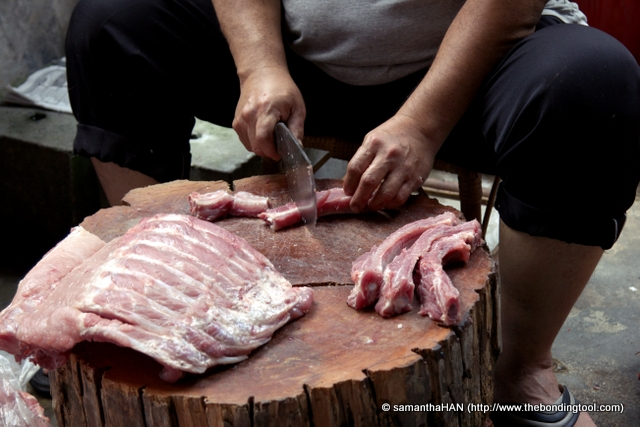 Bags of fresh pork spare ribs were in front of the tree stump he used as chopping board.