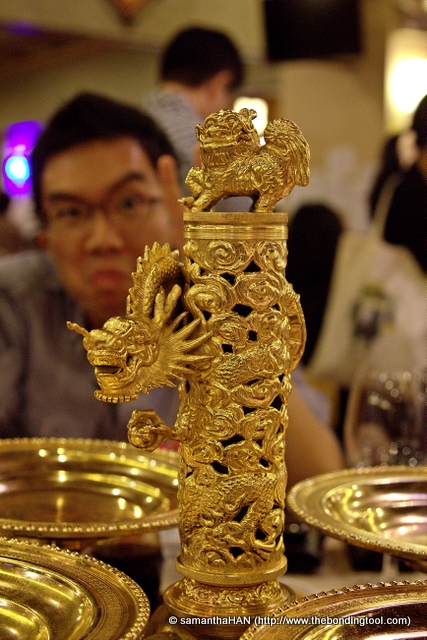 "Back in the main dining hall, the tables were laden with this ""gold"" centrepiece which will hold 4 starter dishes.<br />That's Hungry Cow making funny faces in the bacjgorund. He thought he would be bokeh-ed out but lol..."