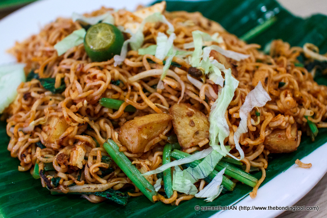 Chi Sao's lunch of Maggi Mee Goreng. Goreng means fry in Malay and Maggi Mee is a brand for instant noodles. So it means Fried Instant (Maggi Mee) Noodles.