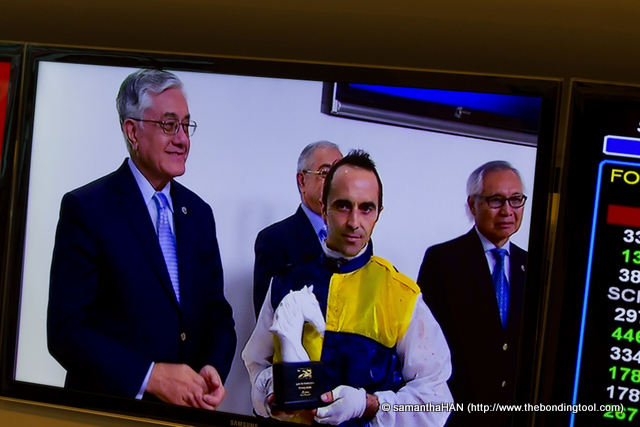While enjoying my tea, I looked up at one of the many screens on the walls and saw Michael (far right) in the Champagne Room downstairs.<br />He was at the presentation of SAAS FEE STAKES (SG3) for the 1400m Short Course race. The prize money was S$200,000.<br />The British jockey was Alan Munro.