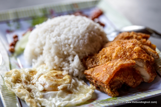 Nasi Lemak with Thigh Meat & Egg Set - MYR5.20.<br />The fried egg was sparingly sprinkled with some white soy sauce, nothing to shout about.<br />The chicken was remarkably crispy on the outside, fully cooked and tender on the inside.<br />There was no traces of blood or pink marrows and the meat seemed rested enough to produce smooth succulent flesh.