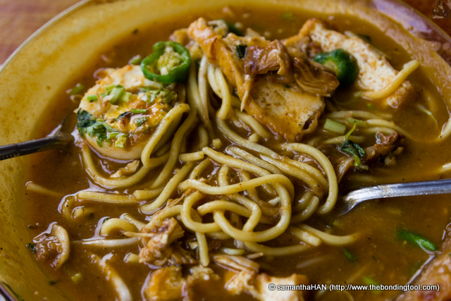 There's half a boiled egg, taukwa (firm beancurd) and chicken.<br />The dish was garnished with crispy shallots, chopped cilantro, cut green chillies and a small lime.<br />The gravy in Mee Rebus is made with mashed potatoes, flour and water.