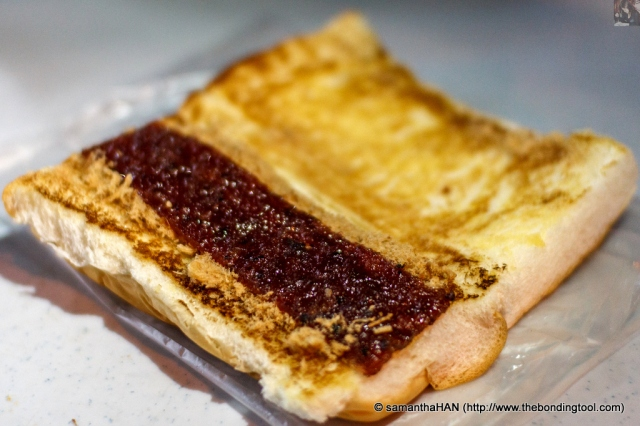 Bun with Pork Floss and Bak Kwa (BBQ Sweet Meat). The red oblong is not strawberry jam but a type of sweet tasting ground meat sheet we called Long Yuk Kon or Dried Dragon's Meat, in Cantonese. Don't worry. No dragons were harmed.  The usual meat used is pork but now we have chicken and beef, too. They can be likened to jerky strips but more tender and sweet.