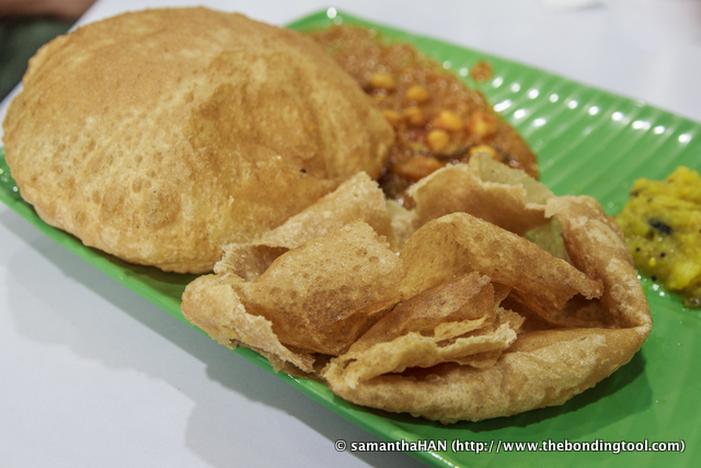 "Puri - S$3.20 Puri (a.k.a. Poori or Boori) is commonly eaten as breakfast or as a light snack. It is also served at special functions or as part of ceremonial rituals along with other vegetarian food in prayer as prasadam. Puri means ""filled"" in Sankrit or ""bread in Georgian. Puri is a wheat dough made of either atta (whole wheat flour), maida (refined wheat flour), or sooji (coarse wheat flour) and salt. The rolled disc is then deep-fried in ghee or vegetable oil. The steam during deep-frying puffs up the dough, hence its shape. Puri is often served with chutneys or some spicy accompaniments i.e. Chholey (spicy chick peas) which I had."