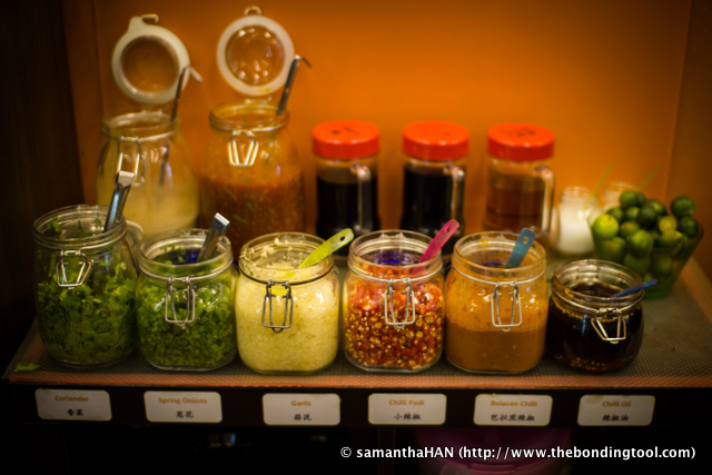 A variety of condiments like pressed garlic, spring onions and sliced chili, to enhance the flavor of the dipping sauces.