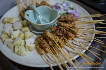 Satay is skewered seasoned meat (usually made of beef, chicken, mutton or pork, sometimes seafood) and served with a dipping sauce of spicy peanut gravy and a side salad of cucumber wedges and raw onions.