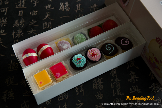 All foods are in even numbers.<br />Top box from left:<br />2 Good Luck Red Eggs.<br />2 Mochi.<br />2 Ang Ku Kuehs.<br />Bottom box from left:<br />2 Fruity Bites.<br />2 Mini Cupcakes.<br />2 Choco Donuts