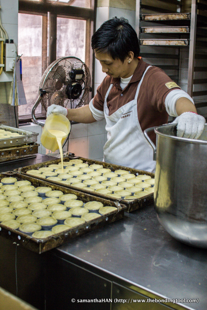 A staff pouring eggy custard into the pastry shells.