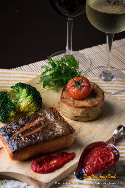 Pan-Seared Salmon with potato & mushroom fondant, broccoli, vine tomato and spicy harissa tomato sauce.